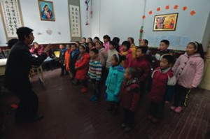 A priest trains children in singing, Taiyuan, Shanxi Province, China