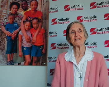 Sister Anne Quinn SMSM before a poster featuring Sister Teresia SMSM and a Jamaican  Family.